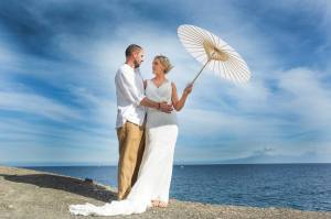 Brie & Groom under parasol by the sea