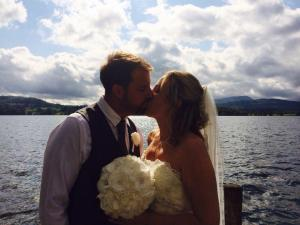 Bridge and groom kissing in front of lake