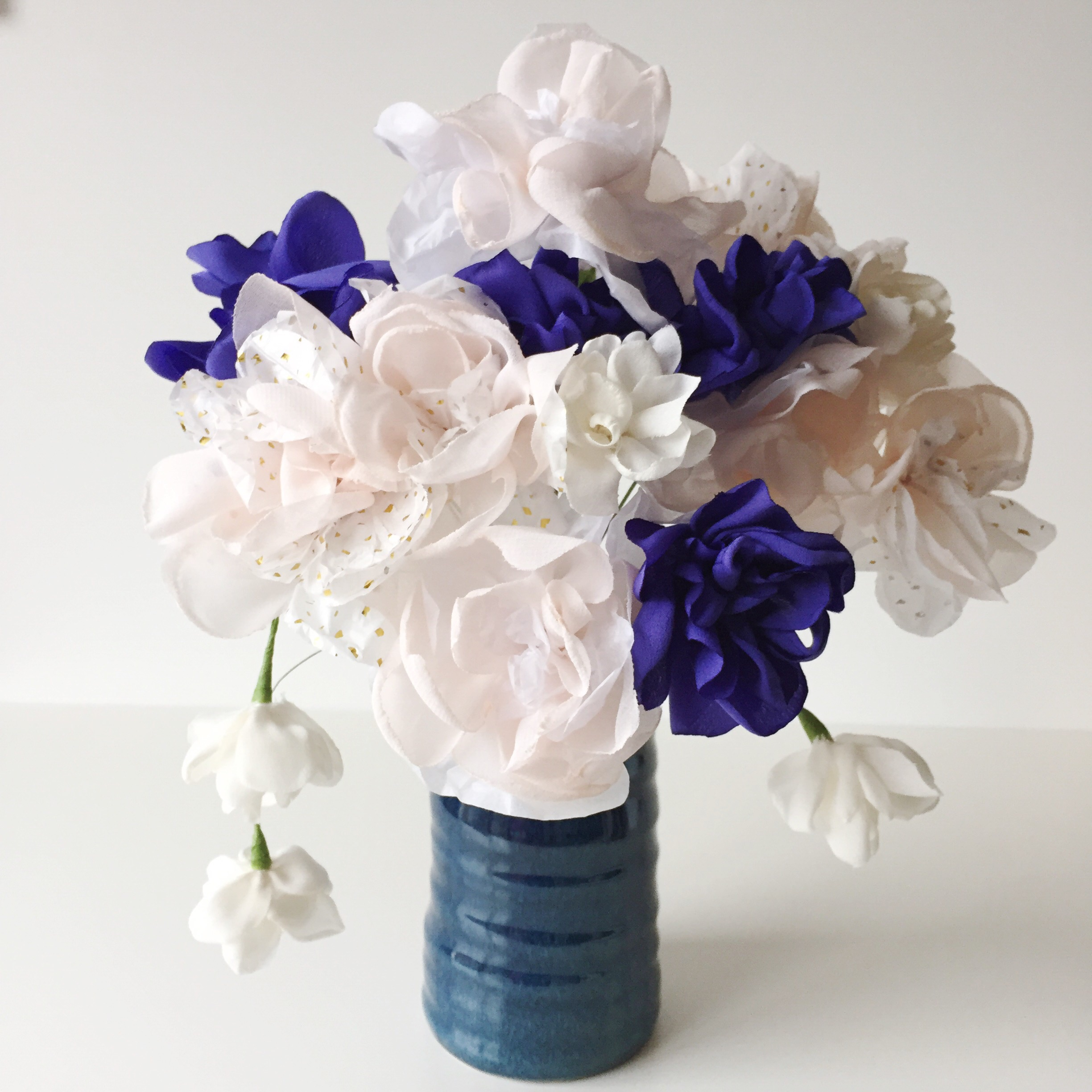 Bunch of hand made fabric and paper azaleas in white and purple displayed in blue vase
