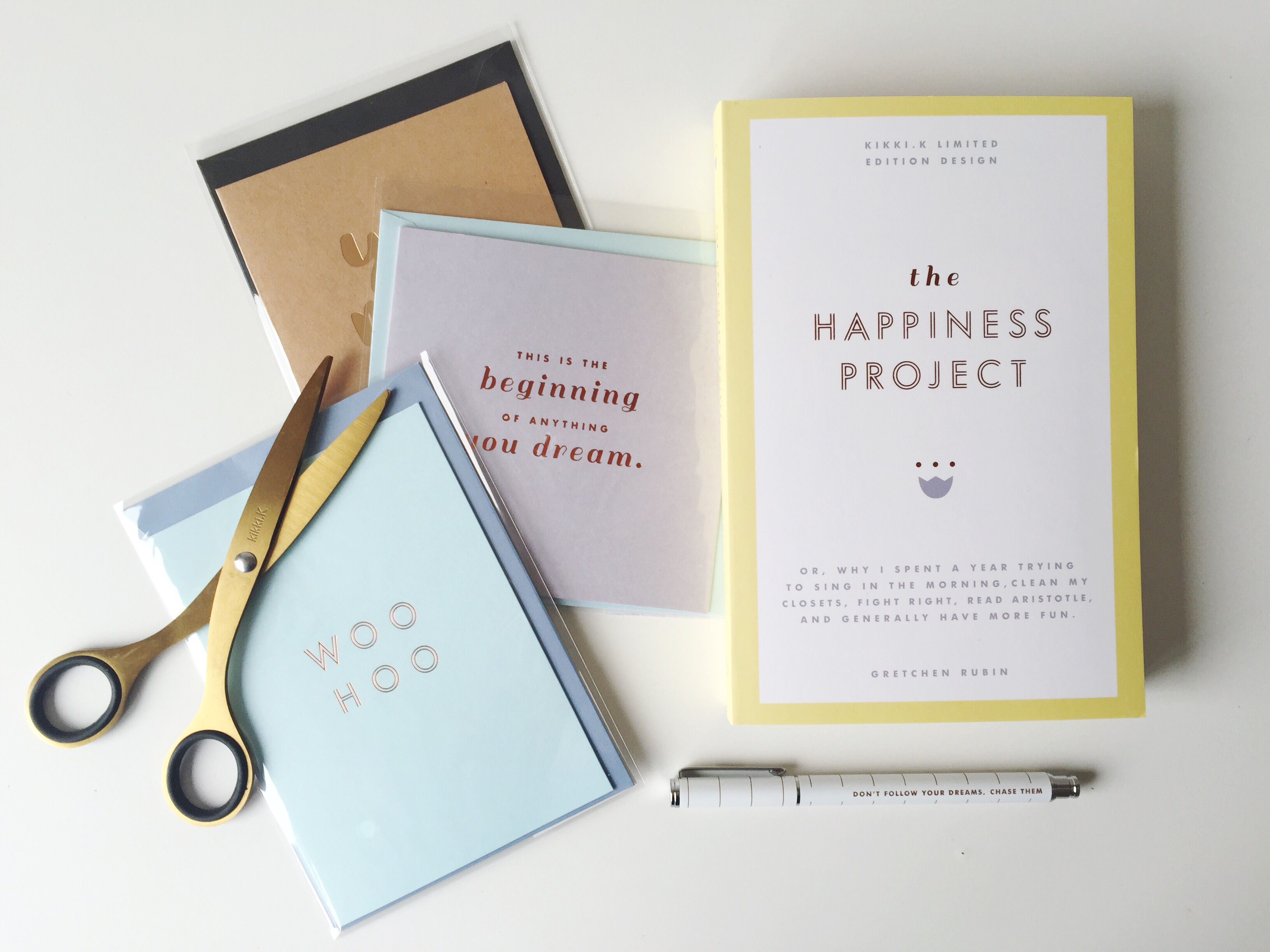 3 cards, Happiness Prject book, gold scissors and a pen laid out on a white desk